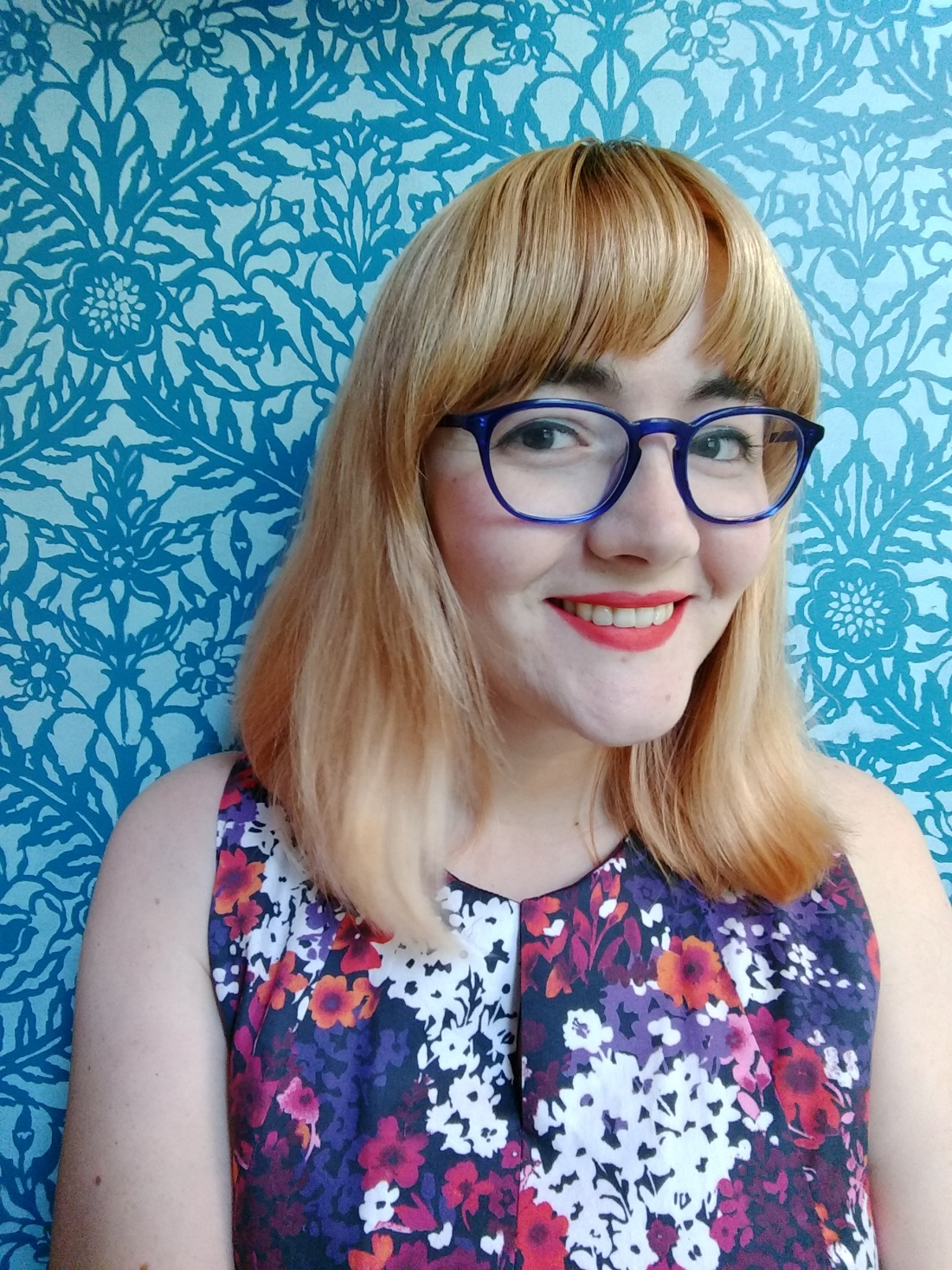 Me wearing a purple floral dress against a blue patterned background. My hair has faded back to blonde.