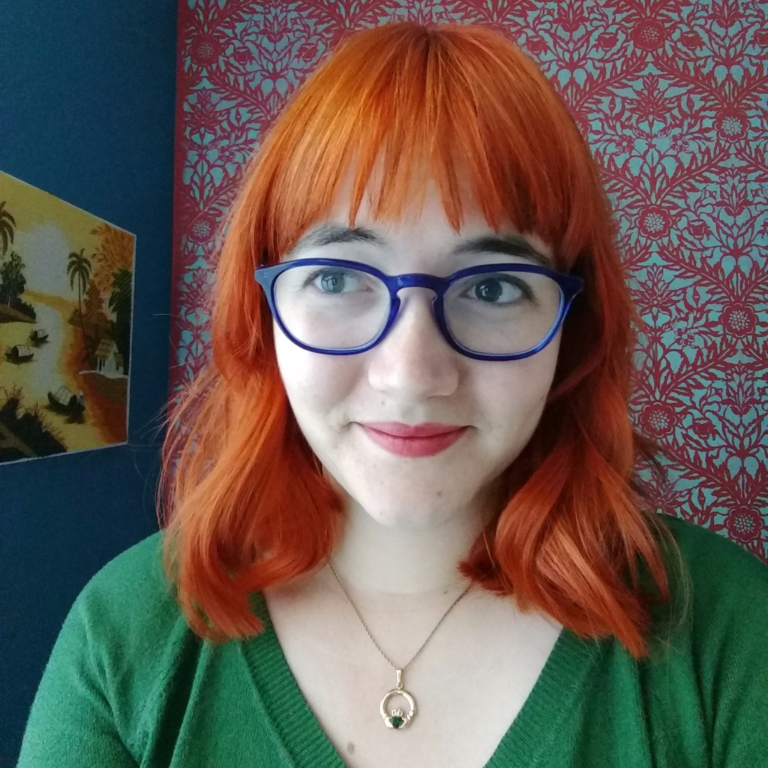 Me with bright copper hair, blue glasses, and a green sweater.