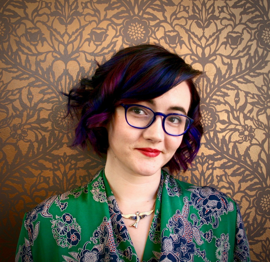 Me with purple hair in front of my gold-stenciled wall wearing a green wrap dress.