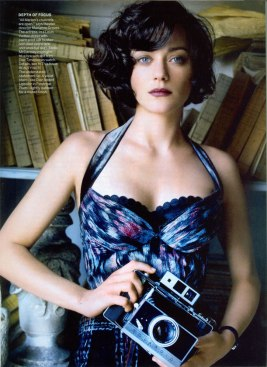 Marion Cotillard standing in front of a book shelf holding an old polaroid camera.