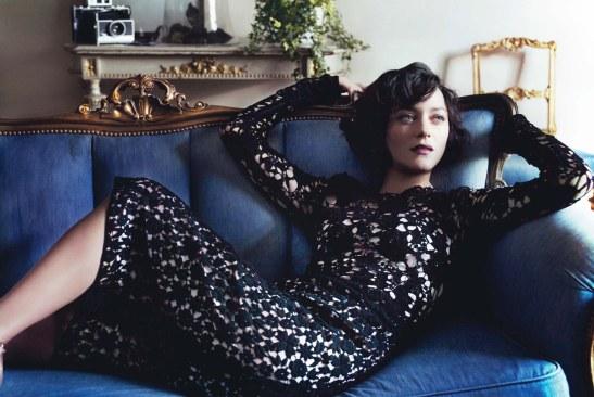Marion Cotillard wearing a black lace dress reclining on a regal-looking sofa.
