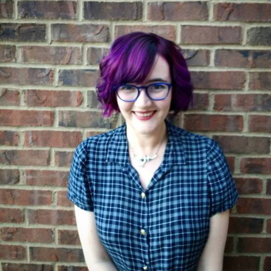 Me, showing off my new purple hair in front of a brick wall.